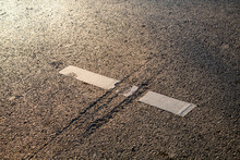 Close Up Of A Scar On Asphalt Road, Dividing A Thermoplastic Road Mark,  Reminding A Jurrasic Attack. Highway Policy, Upkeep, Maintenance Concepts.