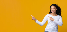 Cheerful Black Young Female Pointing Aside At Free Space On Yellow Background