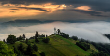 Jamnik, Slovenia - Magical Foggy Summer Morning At Jamnik St.Primoz Hilltop Church. At Sunrise. The Fog Gently Goes Behind The Small Chapel With Golden Sky And Julian Alps At Background