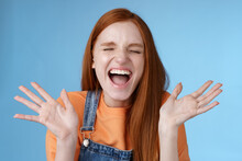 Positive Carefree Triumphing Young Attractive Redhead Girl Scream Out Loud Joy Happiness Close Eyes Waving Raised Hands Win First Prize Dream Come True Celebrating Victory Good News, Blue Background