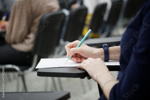 Fényképezés A girl writes a dictation or fills out documents in the audience, sitting on a school chair with a writing stand