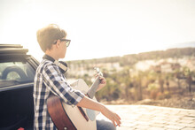 Young Boy Playing Acoustic Guitar Sitting On The Car Trunk Outdoors. Musician Singing On The Road Looking At The Panorama Teen Learning To Play Musical Instrument. Educational Freedom Carefree Concept