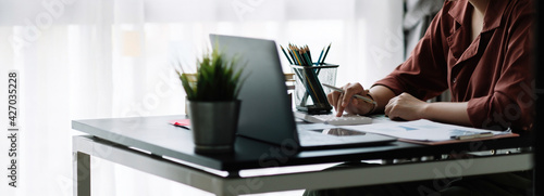 Foto Business woman using calculator for do math finance on wooden desk in office, tax, accounting, statistics home accounring concept