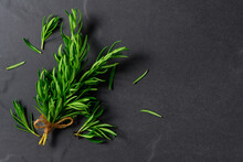 Branch Of Fresh Rosemary On Black Table Background, Herb Concept