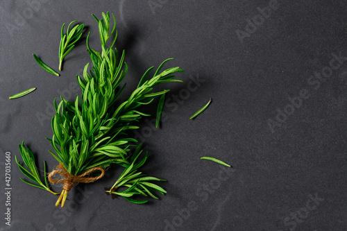 Fototapeta Branch of fresh rosemary on black table background, herb concept obraz