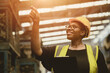 Leinwandbild Motiv Black African professional women worker happy working count checking inventory production stock control in business factory  industry warehouse waring engineer suit and helmet for safety