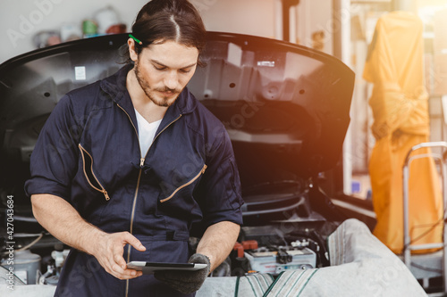 Garage technician worker using tablet computer advance technology for service checking and tuning car ECU at automobile car service center