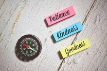 Patience Kindness Goodness Wording With Compass Over A Wooden Background