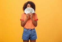 Woman Gonna Waste Lots Of Cash Today. Pleased And Delighted Rich African American Girl With Curly Hairstyle Hiding Face Behind Bunch Of Money Peeking Mysteriously At Camera Winning Millions