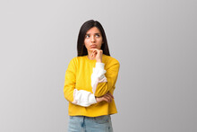 Thoughtful Young Attractive Multi Ethnicity Woman In Trendy Yellow Sweater Against Light Grey Background Holding Her Chin And Looking Up