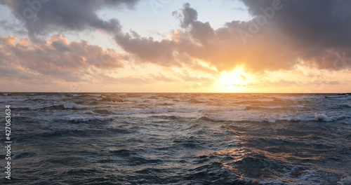 Fototapeta Baltic sea shore under a blue sky with glowing pink and golden sunset clouds after the storm. Crashing waves. Nature, environmental conservation, ecotourism. Picturesque panoramic scenery obraz