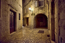 A Narrow Street At Night In One Of The Old Harbor Basins On The Adriatic Coast, Lit By The Scanty Glow Of A Lamp
