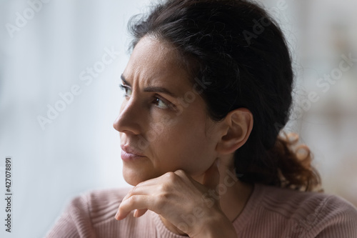 Run of bad luck. Close up of worried thoughtful young hispanic female face look aside prop chin with hand make hard decision. Nervous millennial woman with dark look think consider on serious problem