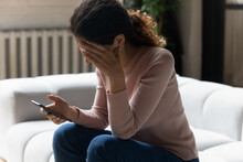 Out Of The Blue. Frustrated Millennial Latin Woman Sit On Sofa Read Sudden Bad News From Cell Screen Cover Face With Palm In Desperate Gesture. Stressed Young Lady Get Nasty Blackmail Message On Email