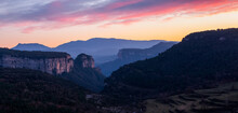 Landscape Of A Valley With Towering Rocky Mountains With A Beautiful Sky With Pink And Orange Clouds At Sunset. Cingles De Tavertet, Collsacabra, Osona, Barcelona, Catalonia, Spain.