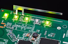 Small Internal Wifi Antenna And Shining LED Lights Embedded On Circuit Board. Light-emitting Diodes, Capacitors And Inductor In Green PCB Detail With Surface-mount Technology Of Electronic Components.