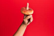 Finger Of Hispanic Man Holding Donut Over Isolated Red Background.
