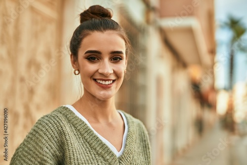 Beautiful brunette woman smiling happy and confident outdoors at the city on a sunny day of autumn - fototapety na wymiar