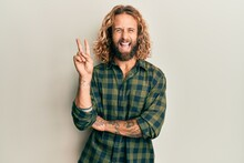 Handsome Man With Beard And Long Hair Wearing Casual Clothes Smiling With Happy Face Winking At The Camera Doing Victory Sign. Number Two.