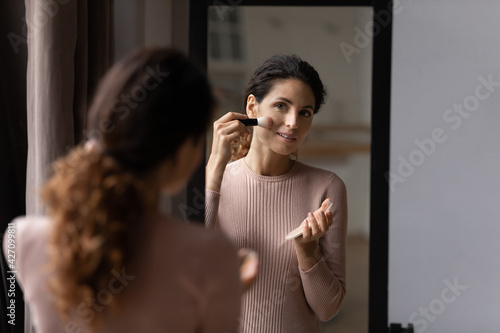Obraz Morning make up. Charming latin female look at mirror hold powder compact container put flour on face with big brush. Happy young woman enjoy visage use professional color cosmetic pressed dry blusher - fototapety do salonu