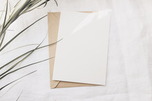 Modern Summer Stationery Still Life. Dry Palm Leaf On White Linen Table Cloth. Blank Greeting Card Mock Up Scene With Craft Envelope In Sunlight. Flat Lay, Top View. Tropical Design. Sun Flare Leaks.