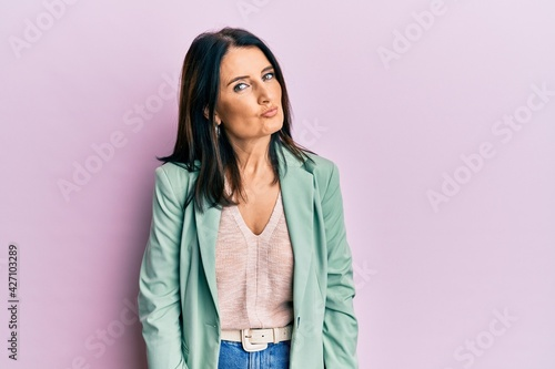 Fotografie, Obraz Middle age brunette woman wearing casual clothes looking at the camera blowing a kiss on air being lovely and sexy