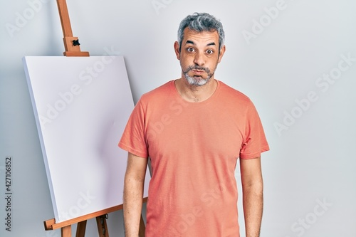 Slika na platnu Handsome middle age man with grey hair standing by painter easel stand puffing cheeks with funny face