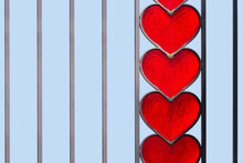 Forged Fence With Red Glass Hearts On A Blue Sky Background