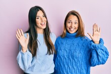 Hispanic Family Of Mother And Daughter Wearing Wool Winter Sweater Waiving Saying Hello Happy And Smiling, Friendly Welcome Gesture