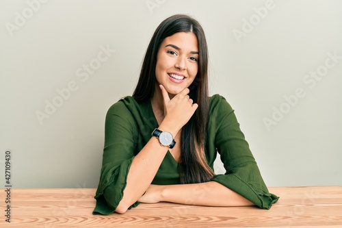 Fotografie, Obraz Young brunette woman wearing casual clothes sitting on the table looking confident at the camera smiling with crossed arms and hand raised on chin