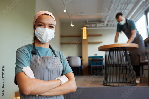 Waist up portrait of young waitress wearing mask and apron looking at camera while standing in cafe with man cleaning tables in background, covid safety measures, copy space