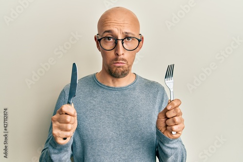 Bald man with beard holding fork and knife ready to eat depressed and worry for distress, crying angry and afraid Fotobehang