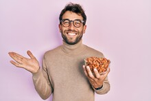 Handsome Man With Beard Holding Peanuts Celebrating Achievement With Happy Smile And Winner Expression With Raised Hand