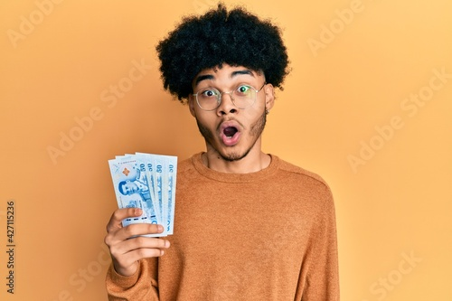 Fényképezés Young african american man with afro hair holding 50 thai baht banknotes scared