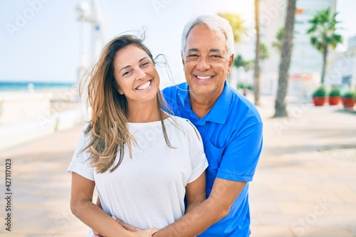 Fotografia Middle age hispanic couple smiling happy hugging at the promenade