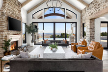 Beautiful Living Room In New Luxury Home. Features Vaulted Ceilings With Wood Beams, Stone Accents, Chandelier, Fireplace With Roaring Fire, And Gorgeous Exterior View With Infinity Pool And Valley.
