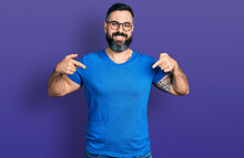 Hispanic Man With Beard Wearing Casual T Shirt And Glasses Looking Confident With Smile On Face, Pointing Oneself With Fingers Proud And Happy.