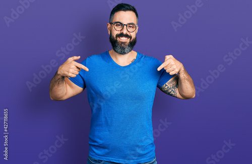 Valokuvatapetti Hispanic man with beard wearing casual t shirt and glasses looking confident with smile on face, pointing oneself with fingers proud and happy