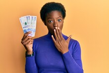Young African American Girl Wearing Doctor Uniform Holding 50 Colombian Pesos Covering Mouth With Hand, Shocked And Afraid For Mistake. Surprised Expression