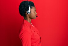Young African American Girl Wearing Call Center Agent Headset Looking To Side, Relax Profile Pose With Natural Face With Confident Smile.
