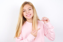 Beautiful Caucasian Little Girl Wearing Pink Hoodie Over White Background Holding An Invisible Aligner And Pointing At It. Dental Healthcare And Confidence Concept.