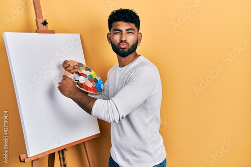 Fotografija Arab man with beard standing drawing with palette by painter easel stand looking at the camera blowing a kiss being lovely and sexy