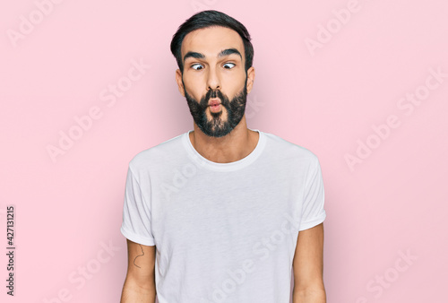 Fotografia Young hispanic man wearing casual white t shirt making fish face with lips, crazy and comical gesture