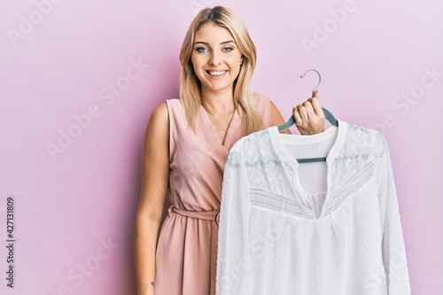 Obraz na plátne Young caucasian woman holding hanger with t shirt looking positive and happy sta