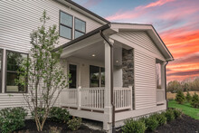 Outdoor Patio Or Sunroom With White Railing, Dark Gutters, White Vinyl Siding With Dramatic Colorful Sunset Background At A American New Real Estate Development In The USA