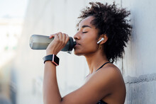 Athletic Woman Drinking Water After Work Out Outdoors.