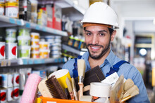 Glad Adult Foreman Standing Near Racks In Paint Store Holding Basket With Tools