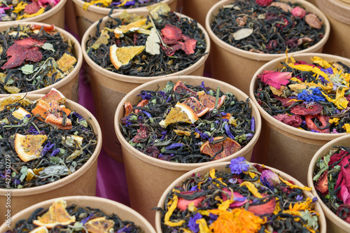 Fototapeta Flower-fruit tea in paper containers. Dry slices of lemon, orange, strawberry. Red, yellow, lilac petals of healing and fragrant flowers and herbs. obraz