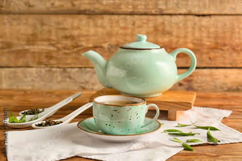 Cup and teapot of green tea on wooden background