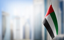 A Small Flag Of United Arab Emirates On The Background Of A Blurred Background